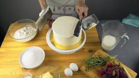 Zettend boterroomcake die met de hand spatel gebruiken stock video