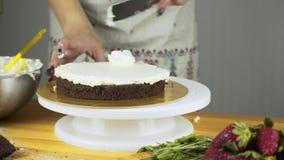 Zettend boterroomcake die met de hand spatel gebruiken stock footage