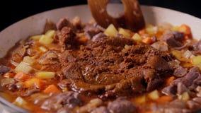 Zettend de kerrieroux in pan en dan mengeling met rundvlees, aardappel en wortel stock videobeelden