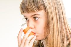 Zeven éénjarigenmeisje die astmatische inha van de geneeskundegezondheidszorg ademen stock foto