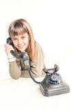 Zeven éénjarigenmeisje met oude uitstekende telefoon vóór witte backgrou Stock Foto