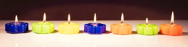 Zeven brandende kaarsen op een rij Stock Fotografie