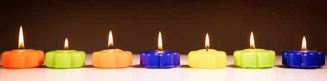 Zeven brandende kaarsen op een rij Stock Foto