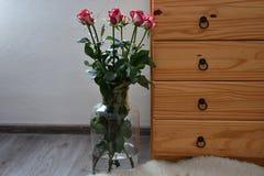 Zeven die boeketten van rozen in een vaas met houten opmakers wordt gebouwd Stock Foto