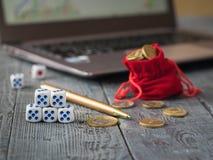 Zeven dobbelen en een stapel van muntstukken voor laptop met bedrijfsprogramma's Royalty-vrije Stock Afbeeldingen