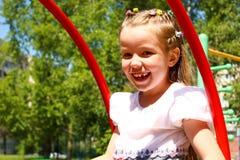 Zeven-jaar-oud meisje die op een schommeling slingeren Royalty-vrije Stock Foto