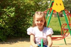 Zeven-jaar-oud meisje op een schommeling Stock Afbeelding