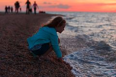 Zeven jaar oud meisjes op het strand in zonsondergangtijd Royalty-vrije Stock Fotografie
