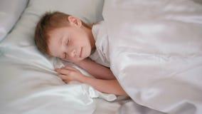 Zeven-jaar-oude jongens aardige slaap in zijn bed stock video