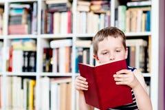 Zeven jaar oude jongens die een boek in bibliotheek lezen Stock Foto