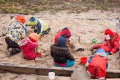 Zeven kleine jonge geitjes die in dag van de zandbak de bewolkte herfst spelen Royalty-vrije Stock Fotografie