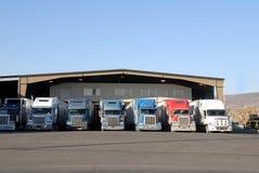 Zeven vrachtwagens bij pakhuis Royalty-vrije Stock Afbeeldingen