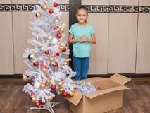 Zevenjarige meisjestribunes in een doos met Kerstmisspeelgoed en Kerstboom Stock Foto's