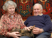 Zeventig éénjarigenpaar dat in huis op bank glimlacht Royalty-vrije Stock Foto