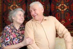 Zeventig éénjarigenpaar dat thuis glimlacht Stock Fotografie
