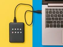 Zewnętrznie dysk twardy łączył laptop na błękitnym i żółtym tle Mieszkanie nieatutowy Poj?cie pomocniczy magazyn obrazy royalty free