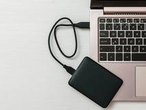 Zewnętrznie dysk twardy łączył laptop na lekkim biurku Mieszkanie nieatutowy Pojęcie pomocniczy magazyn fotografia stock