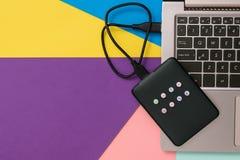 Zewnętrznie dysk twardy z laptopem na kolorowym tle Mieszkanie nieatutowy Poj?cie pomocniczy magazyn zdjęcie royalty free