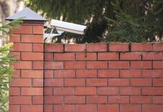 Zewnętrznie inwigilaci kamera nad ceglanym ogrodzeniem własność prywatna Systemy bezpieczeństwa ochrona, wideo inwigilacja fotografia royalty free