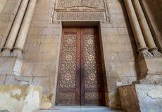 Zewnętrznie stara dekorująca cegły kamienna ściana z arabesk dekorującym drewnianym drzwi obramiającym kamiennymi ozdobnymi cylin zdjęcia stock