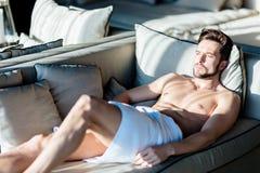 Zezowań potomstwa, piękny męski relaksować na leżance w hotelu Obrazy Stock