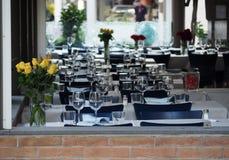Zgłasza set w restauraci moment przed, nawadnia gl, Dekoracyjnymi koloru żółtego i czerwieni kwiatami, win szkła i fotografia royalty free