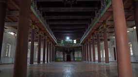 Zharkent Mosque. Low angle view of the prayers hall with red colored columns and ornamented ceiling with lantern stock footage