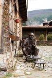Zheravna,保加利亚小店13日2016年:一个人的铜雕塑、雕象坐椅子和饮用的咖啡 库存照片