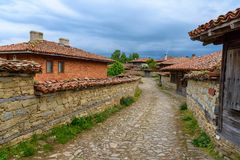 Cobbled street and rustic houses in Zheravna, Bulgaria. Zheravna, Bulgaria - architectural reserve of rustic houses and narrow cobbled streets from the Bulgarian stock photography