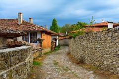 Cobbled street and rustic houses in Zheravna, Bulgaria. Zheravna, Bulgaria - architectural reserve of rustic houses and narrow cobbled streets from the Bulgarian stock image