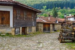 Cobbled street and rustic houses in Zheravna, Bulgaria. Zheravna, Bulgaria - architectural reserve of rustic houses and narrow cobbled streets from the Bulgarian royalty free stock photos