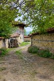 Cobbled road, old traditional houses and walnut tree branches in Zheravna, Bulgaria. Zheravna, Bulgaria - narrow cobbled road and rustic houses framed in walnut royalty free stock photo