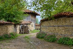 Cobbled road, old traditional houses and walnut tree branches in Zheravna, Bulgaria. Zheravna, Bulgaria - narrow cobbled road and rustic houses framed in walnut stock photography