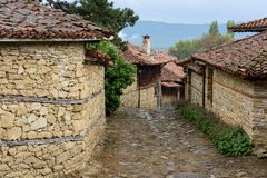Cobbled road and old traditional houses in Zheravna, Bulgaria. Zheravna, Bulgaria - narrow cobbled road and rustic traditional houses made of stone and wood with royalty free stock image