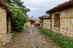 Cobbled road and old traditional houses in Zheravna, Bulgaria. Zheravna, Bulgaria - narrow cobbled road and rustic traditional houses made of stone and wood with royalty free stock images