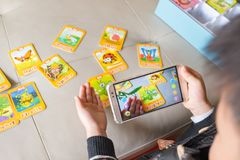 Zhongshan,China-December 30, 2017:kid playing Augmented Reality popup of praying mantis via mobile. AR and VR games become more and more popular royalty free stock photos