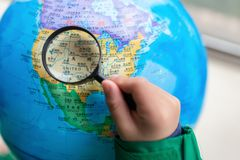 Kid looking at the map of the US on a globe with magnifier. Zhongshan,China-February 7, 2018:kid looking at the map of the US on a globe with magnifier royalty free stock photo