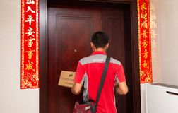 Male courier from JD.com delivering a parcel to the customers home. Zhongshan,China-June 3,2018:male courier from JD.com delivering a parcel to the customers stock images
