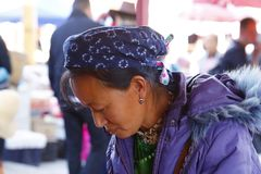 A woman of an ethnic minority of Yunnan with her traditional clothes in the market of Zhoucheng village, Dali, Yunnan, China stock photo
