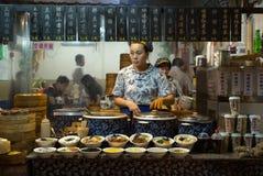 ZHOUZHUANG, CHINY: Sklep spożywczy w tradycyjnym kulturalnym tytułowaniu sprzedaje gorących foods i napój obraz royalty free