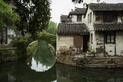 ZHOUZHUANG KINA: Gamla hus och broreflexion i en bykanal royaltyfri foto