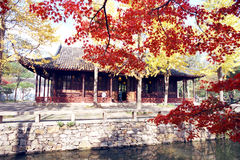 Zhuozhengyuan Garden. Eastern park, in the autumn, yellow and crimson leaves and a lakeside wooden house set off each other. is a classical Chinese garden, and Royalty Free Stock Image