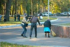 ZHYTOMYR, ΟΥΚΡΑΝΙΑ - 10 Οκτωβρίου 2014: Άνθρωποι από τα μέσα που ρωτούν τη ηλικιωμένη γυναίκα ενώ σκουπίζει το πάτωμα σε μια οδό Στοκ φωτογραφίες με δικαίωμα ελεύθερης χρήσης