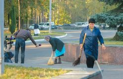 ZHYTOMYR, ΟΥΚΡΑΝΙΑ - 10 Οκτωβρίου 2014: Άνθρωποι από τα μέσα που ρωτούν τη ηλικιωμένη γυναίκα ενώ σκουπίζει το πάτωμα σε μια οδό Στοκ Εικόνες
