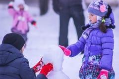 Zhytomyr, de Oekraïne - Januari 11, 2016: De familie maakt sneeuwman Stock Fotografie