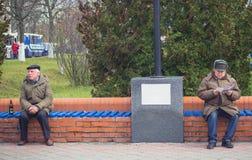 Zhytomyr, de Oekraïne - Oktober 19, 2015: Twee hogere heren die en op een houten bank in een park zitten ontspannen Stock Afbeeldingen