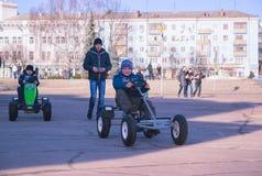 Zhytomyr, Ucrânia - 5 de maio de 2015: Dois meninos das crianças na roupa colorida e em conduzir carros do brinquedo foto de stock royalty free
