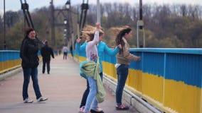 Zhytomyr, Ucrania - 17 de abril de 2016: El fuerte viento sopla a muchachas del puente almacen de metraje de vídeo