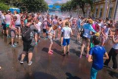 Zhytomyr, Ucrania - 25 de junio de 2016: la muchedumbre feliz de la gente que va de fiesta debajo de la nube colorida del polvo f Imagenes de archivo