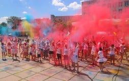Zhytomyr, Ucrania - 25 de junio de 2016: la muchedumbre feliz de la gente que va de fiesta debajo de la nube colorida del polvo f Imagen de archivo libre de regalías
